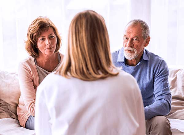 Dementia caretaker speaking with a couple